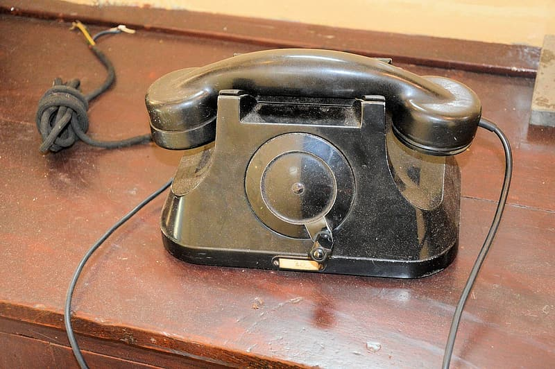 Black rotary phone on brown wooden table