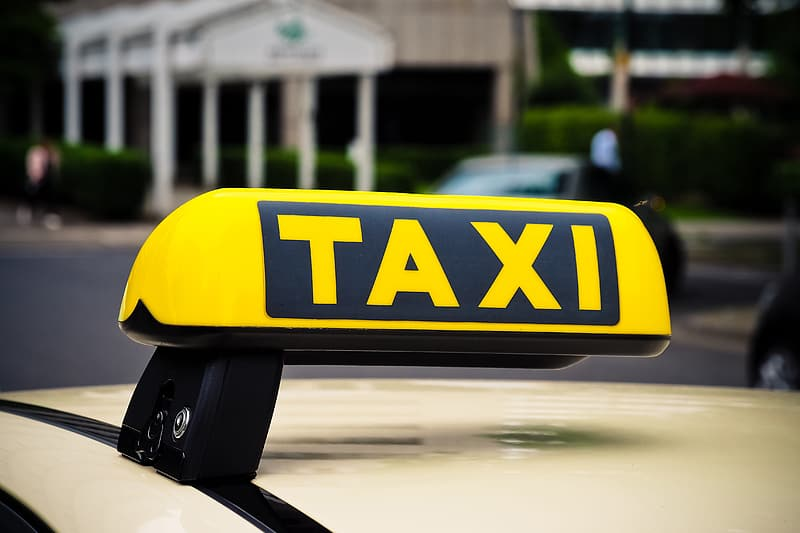 Yellow and black Taxi signage