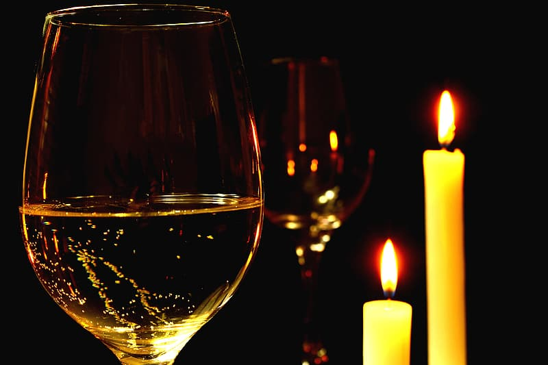 Two wine glasses beside two taper candles
