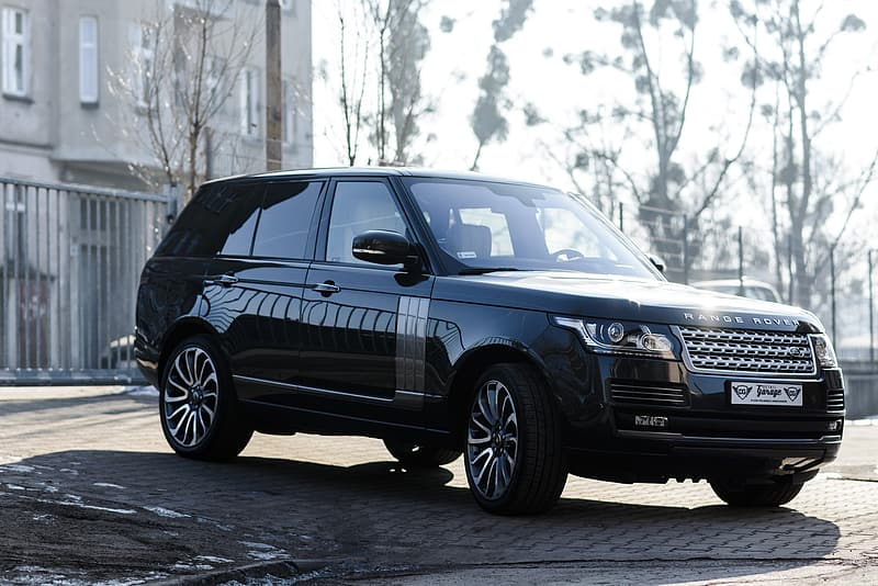 Black Land Rover Range Rover SUV parked on pavement near fence and buildin