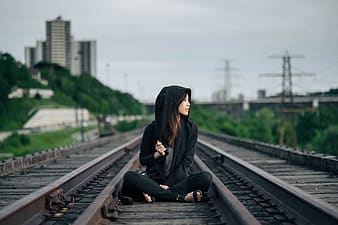 Woman in black hoodie sitting on train rail during daytime