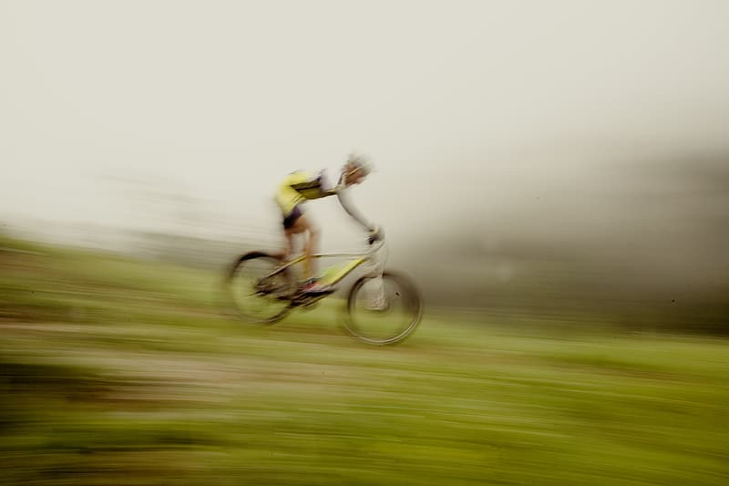 Man riding yellow bicycle on green grass