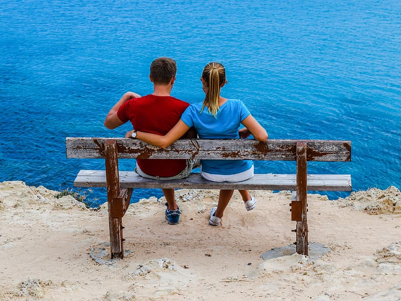 Couple sitting on beige wooden bench on cliff by the water during daytime