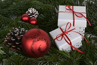 Three red baubles with two white gift boxes