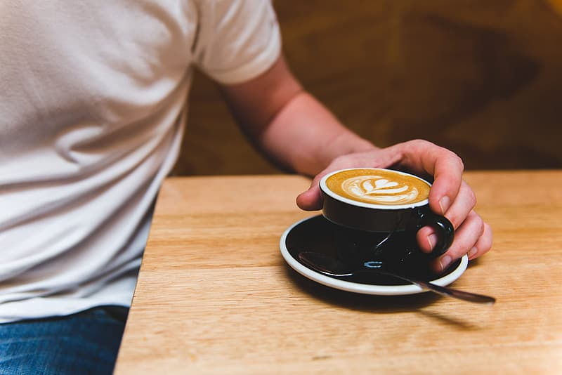 Person holding teacup filled of coffee