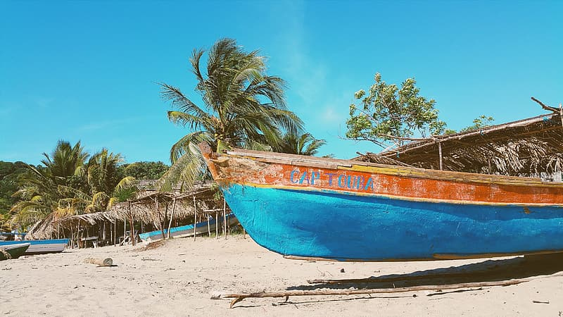 Brown and blue wooden canoe on sand under blue sky during daytime