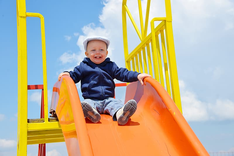Boy sitting on outdoor play slide
