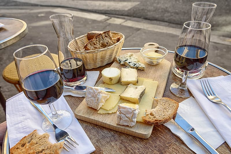 Clear short-stemmed wine glasses, sliced breads, brown wooden chopping board, and brown wicker basket on brown wooden table