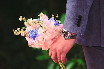 Person holding pink and white flower bouquet
