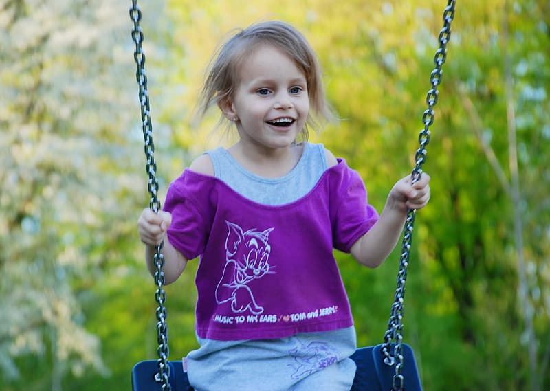 Girl in purple sweater sitting on swing during daytime