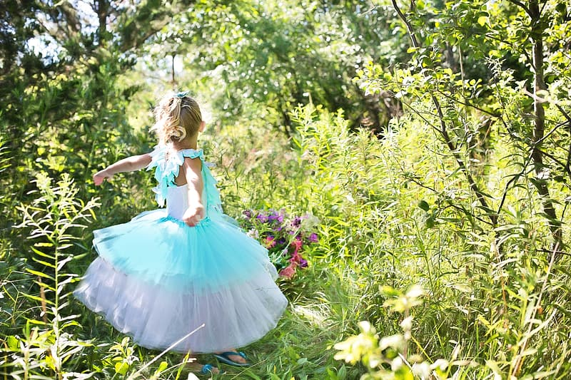 Girl wearing blue and white tutu dress standing on grass