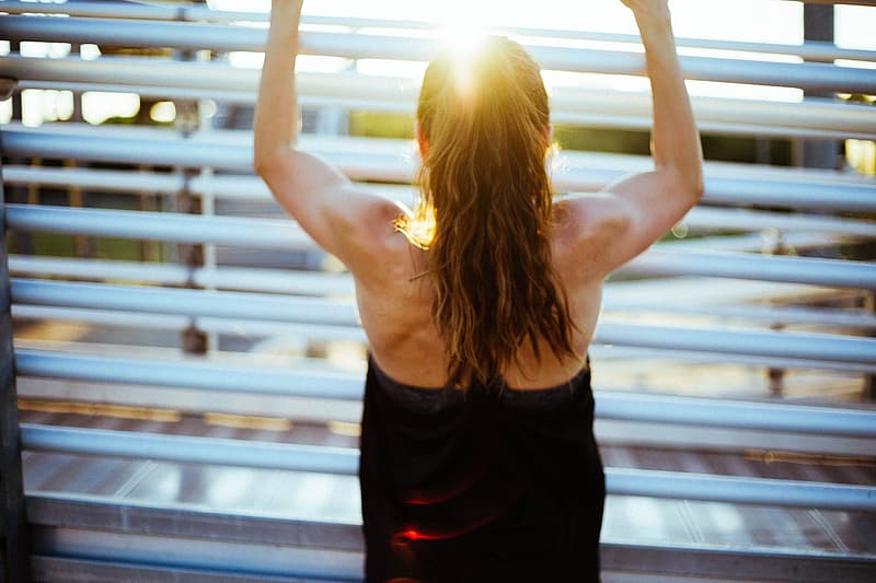 Woman in black tank top and black shorts raising her hands