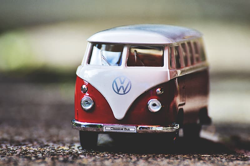 White and red Volkswagen T1 scale model on gray dirt selective focus photography
