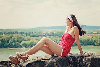 Woman in red tank top sitting on rock during daytime