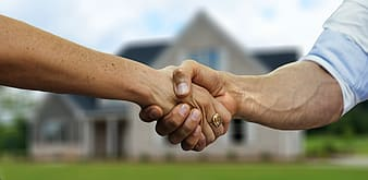 Two people shaking hands during daytime