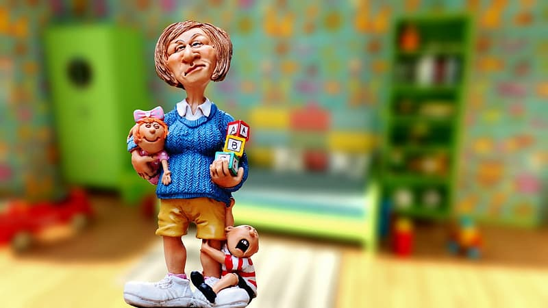 Woman carrying baby and alphabet blocks figurine