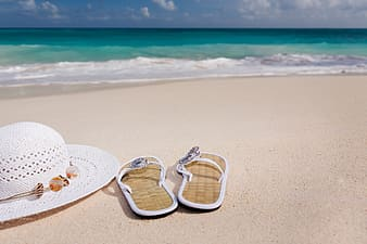 Pair of brown flip flops beside white sunhat