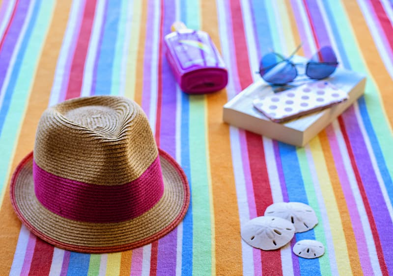 Brown and pink hat and blue aviator-style sunglasses