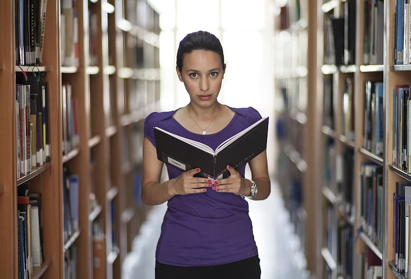 Woman in purple top holding book in library