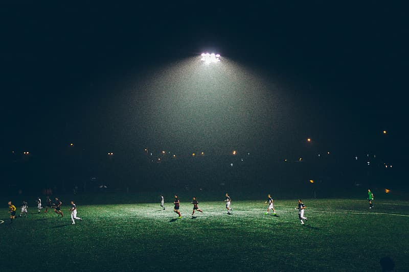 People playing soccer on field during night time