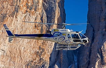White and blue helicopter flies near brown rock formation