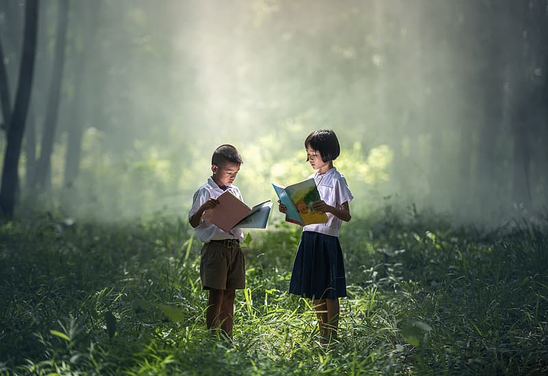 Girl and boy holding book while standing in grass field