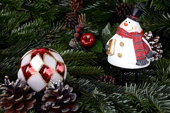 Two white-and-red Christmas bauble near snowman ornaments