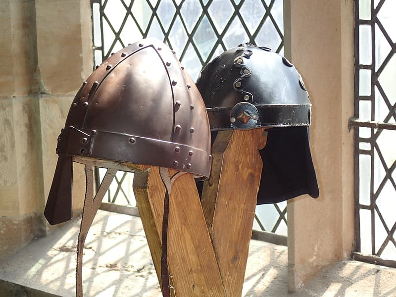 Two brown knight helmets on brown stand