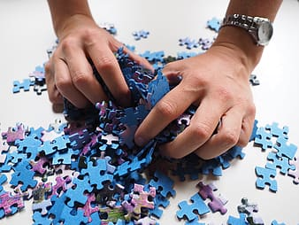 Person picking jigsaw puzzles