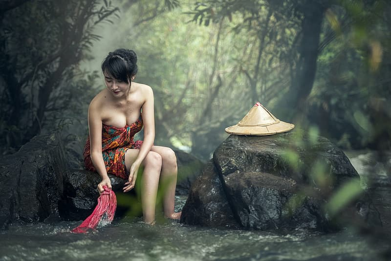 Woman in red strapless dress sitting on rock in water