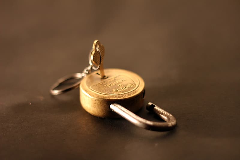Gold-colored padlock with grey metal key