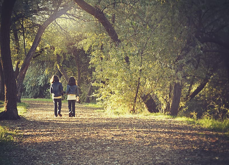 Two girl wearing blue denim jackets walking on the forest