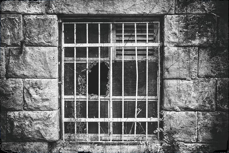 Grayscale photo of window grill and wrecked window screen