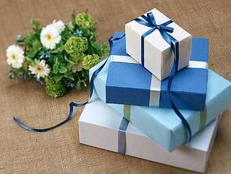 Stack of four assorted-color gift boxes beside white and green petaled flower bouquet