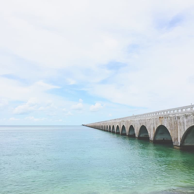 Gray concrete bridge over blue sea under white sky during daytime