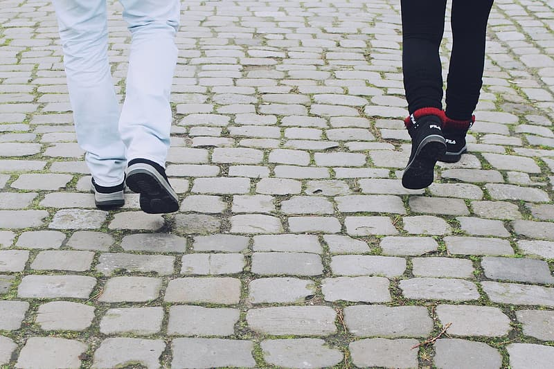 Two person wearing white and black pants and sneakers walking on pavement
