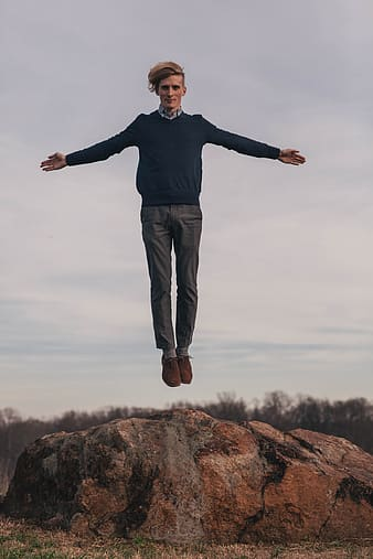 Man in black sweater and brown pants standing on brown rock during daytime