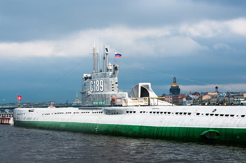 White and green ship on sea under gray sky
