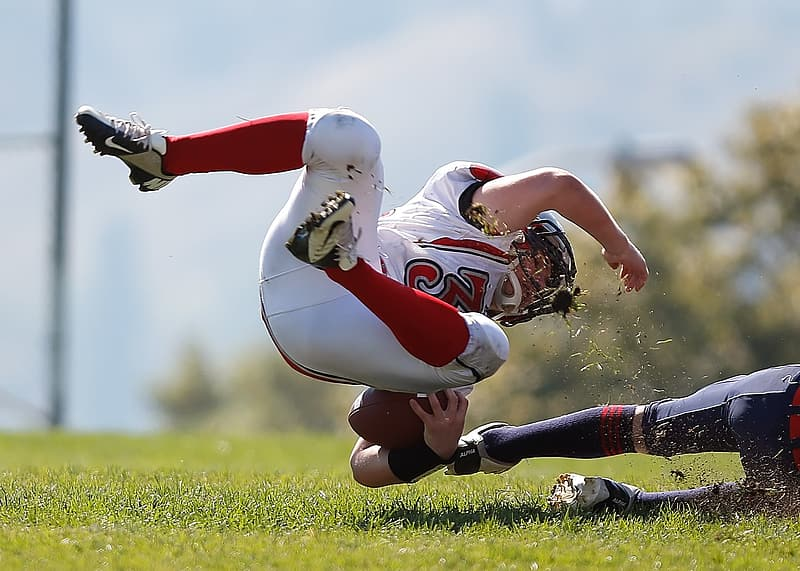 Depth of field photography of american football athlete about to fall on ground