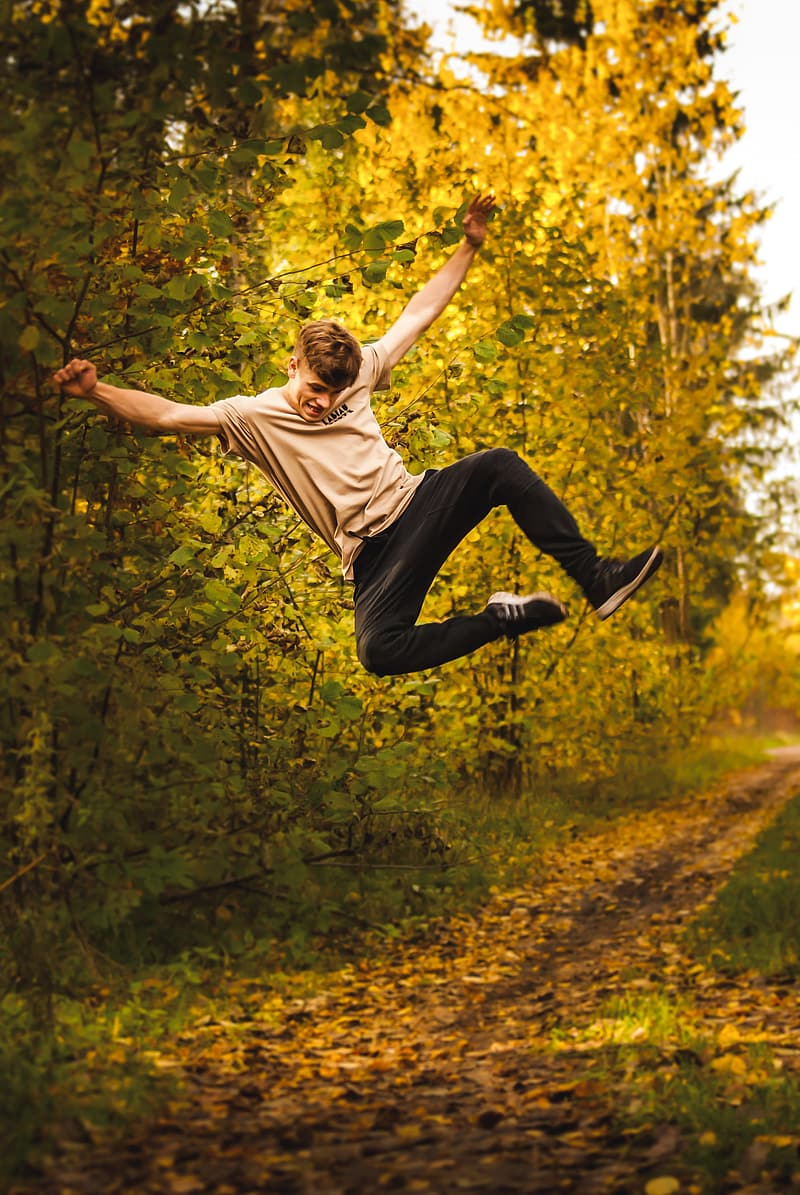 Man in brown t-shirt and black pants jumping on forest during daytime