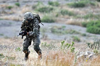 Man wearing brown and gray camouflage overalls running uphill while holding SMG during daytime