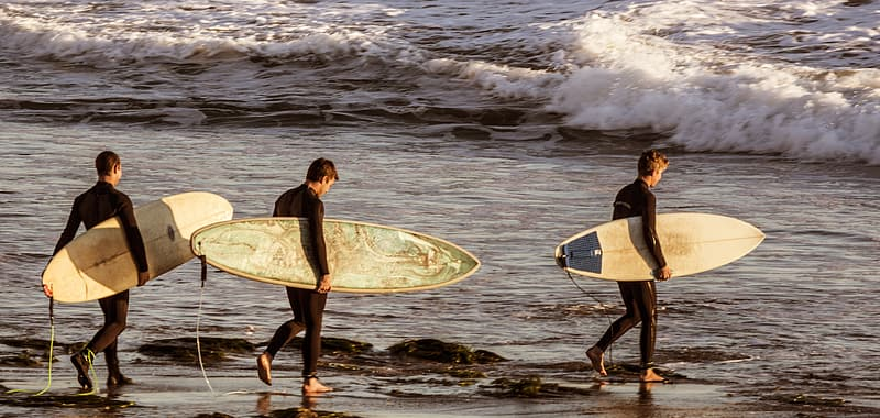 Three surfers carrying beige surfboards at beach