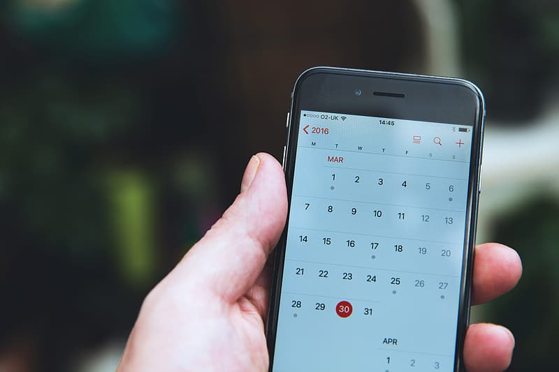 Man checking the calendar app on his iPhone mobile smartphone