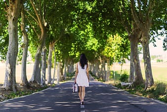 Woman in white dress walking on road at daytime