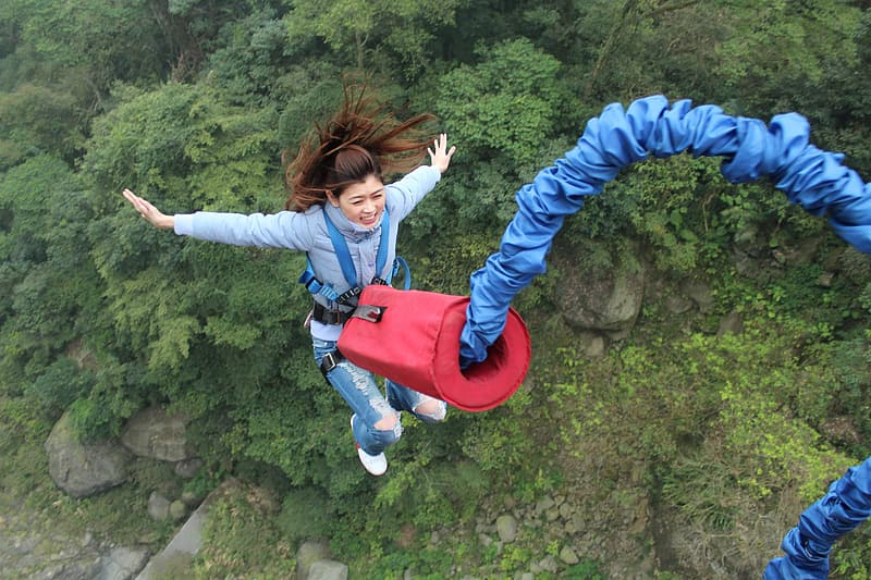 Girl in red and blue jacket and blue denim jeans jumping on brown rock during daytime