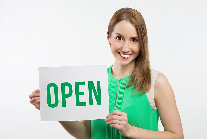 Woman in green and white sleeveless shirt holding white and green card with open text