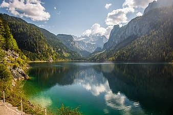 Green lake surrounded by green trees and mountains under blue sky during daytime