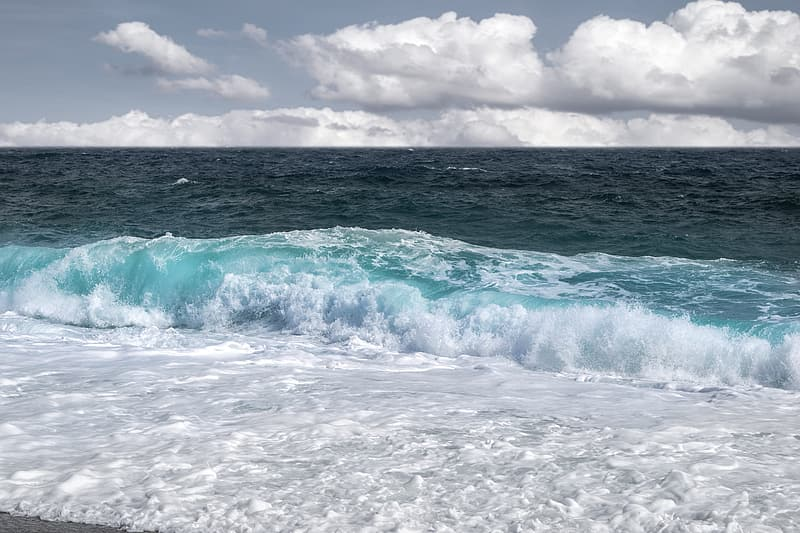 Ocean waves under white clouds during daytime