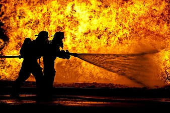 Two fireman blowing water using hose on fire