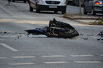 Black and blue motorcycle crash on road